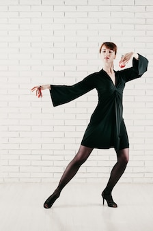 Joven mujer atractiva en vestido negro, bailando con castañuelas rojas