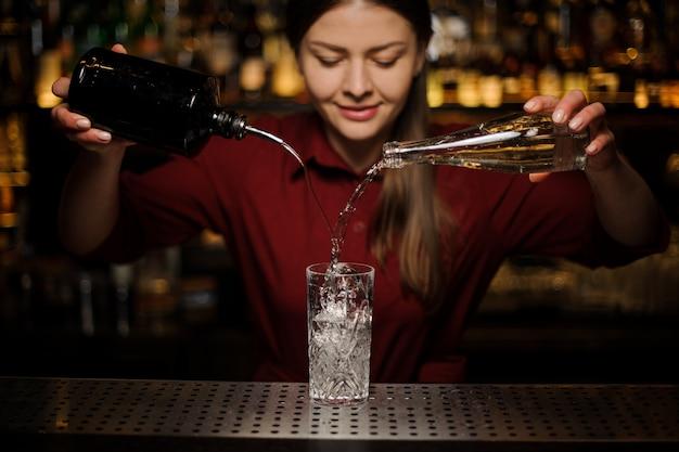 Joven mujer barman macetas ginebra y jarabe dulce en un vaso
