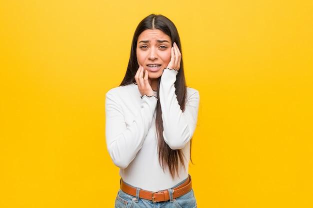 Joven mujer bastante árabe contra un fondo amarillo lloriqueando y llorando desconsoladamente.