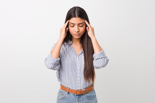 Joven mujer bastante árabe tocando las sienes y teniendo dolor de cabeza.