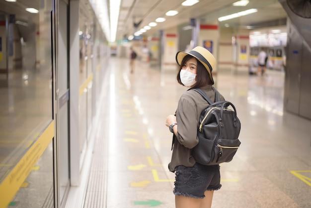 Una joven mujer bastante asiática lleva una máscara protectora de pie en la estación de metro