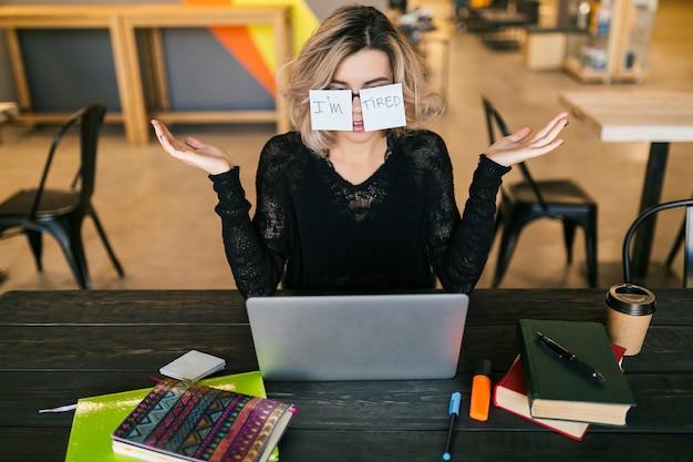Joven mujer bastante cansada con pegatinas de papel en vasos sentado a la mesa en camisa negra trabajando en equipo portátil