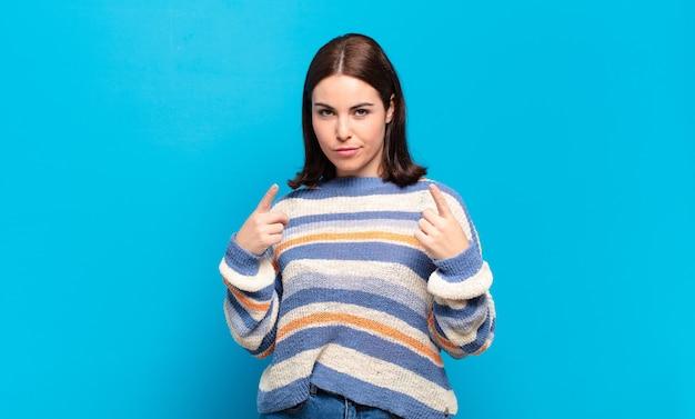 Joven mujer bastante casual con una mala actitud que parece orgullosa y agresiva, apuntando hacia arriba o haciendo un signo divertido con las manos