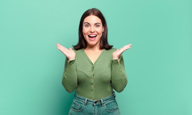Joven mujer bastante casual que parece feliz y emocionada, sorprendida con una sorpresa inesperada con ambas manos abiertas junto a la cara