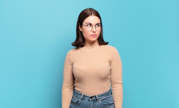 Joven mujer bastante casual que parece perpleja y confundida, preguntándose o tratando de resolver un problema o pensando