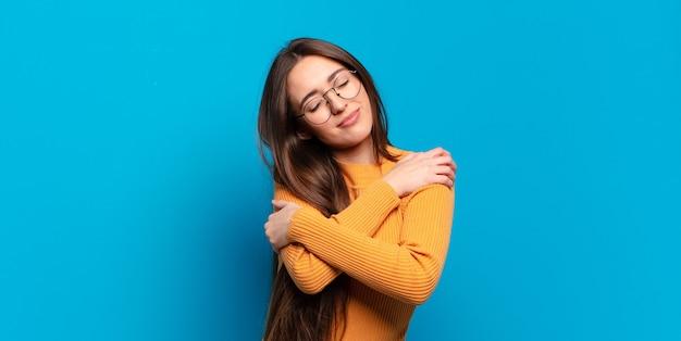 Joven mujer bastante casual que se siente enamorada, sonriendo, abrazándose y abrazándose a sí misma, permaneciendo soltera, siendo egoísta y egocéntrica