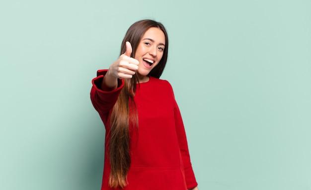 Joven mujer bastante casual que se siente orgullosa, despreocupada, segura y feliz, sonriendo positivamente con los pulgares hacia arriba