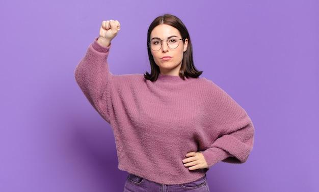 Joven mujer bastante casual que se siente seria, fuerte y rebelde, levantando el puño, protestando o luchando por la revolución