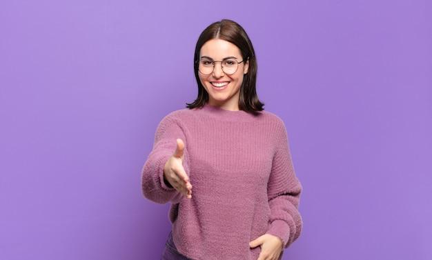 Joven mujer bastante casual sonriendo, luciendo feliz, confiada y amigable, ofreciendo un apretón de manos para cerrar un trato, cooperando