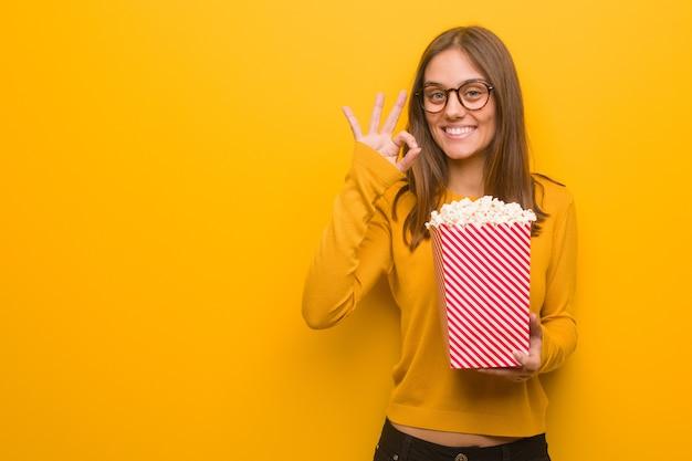 Joven mujer bastante caucásica alegre y confiada haciendo gesto bien. ella está comiendo palomitas de maíz.