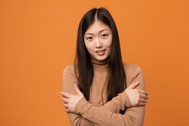 Joven mujer bastante china va frío debido a la baja temperatura o una enfermedad.