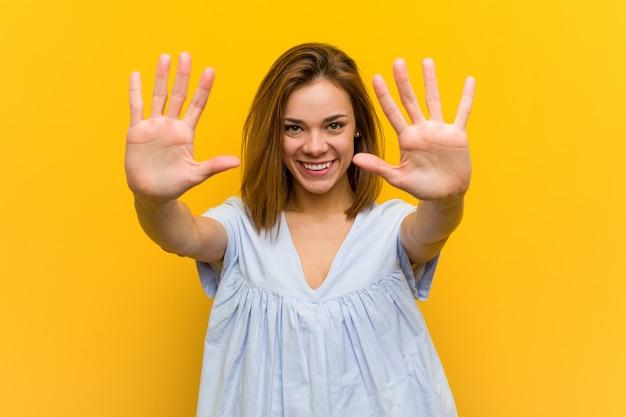 Joven mujer bastante joven que muestra el número diez con las manos.