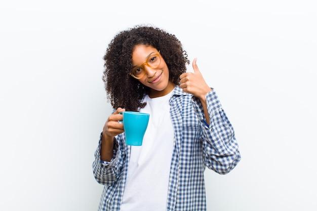 Joven mujer bastante negra con un café contra la pared blanca