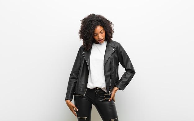 Joven mujer bastante negra con una chaqueta de cuero sobre pared blanca