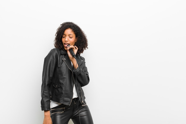 Joven mujer bastante negra con un micrófono con una chaqueta de cuero