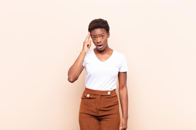 Joven mujer bastante negra que parece sorprendida, con la boca abierta, conmocionada, dándose cuenta de un nuevo pensamiento, idea o concepto