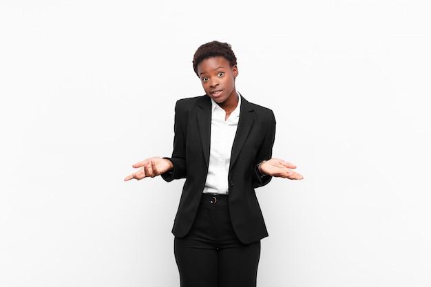 Joven mujer bastante negra que se siente desorientada y confundida, no está segura de qué opción u opción elegir, preguntándose contra la pared blanca
