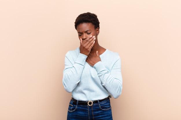 Joven mujer bastante negra que se siente enferma con dolor de garganta y síntomas de gripe, tos con la boca cubierta
