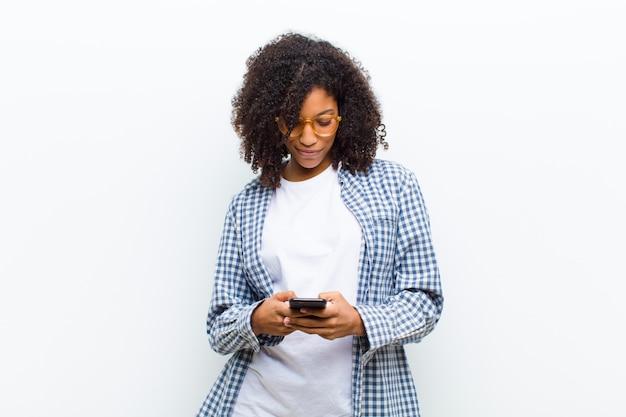 Joven mujer bastante negra con un teléfono inteligente contra la pared blanca
