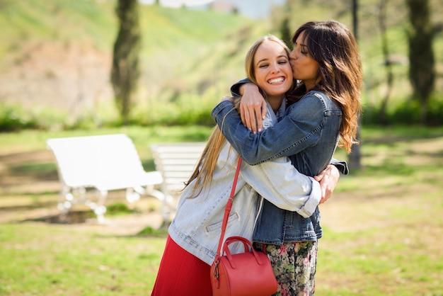 Joven mujer besando la cara de su amigo al aire libre.