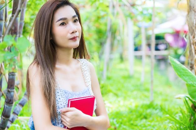 Joven mujer bonita abrazo un diario en el brazo