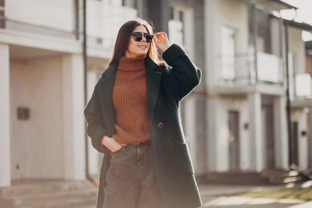 Joven mujer bonita en abrigo cálido junto a la casa
