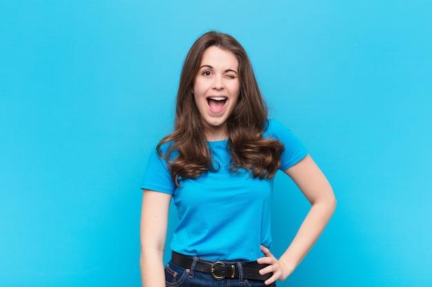 Joven mujer bonita con actitud alegre, despreocupada, rebelde, bromeando y sacando la lengua, divirtiéndose contra la pared azul