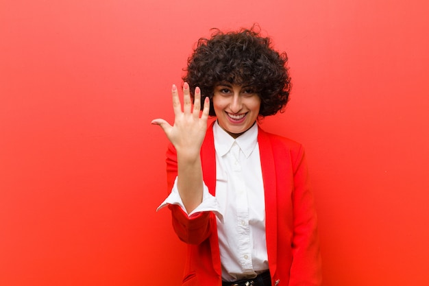 Joven mujer bonita afro sonriendo y mirando amigable, mostrando el número cinco o quinto con la mano hacia adelante, cuenta atrás