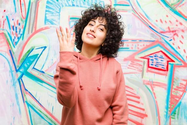 Joven mujer bonita afro sonriendo y mirando amigable, mostrando el número cuatro o cuarto con la mano hacia adelante, contando en contra del graffiti