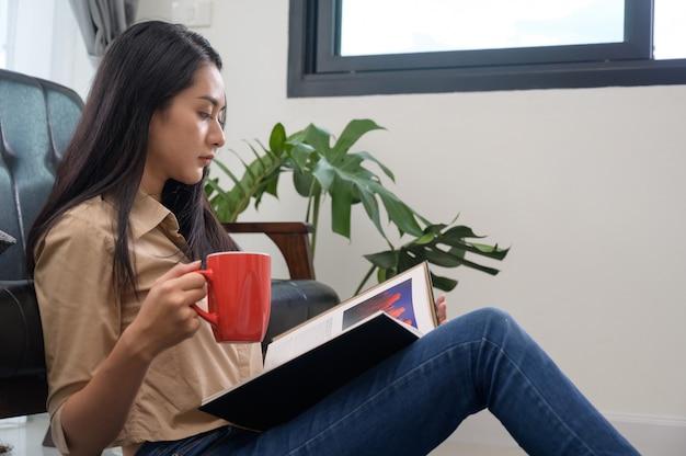 Joven mujer bonita asiática piel blanca sentada tomando café y leyendo un libro disfruta de descanso