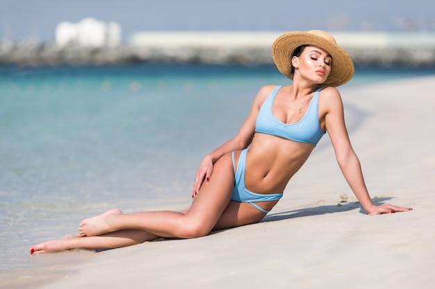 Joven mujer bonita en bikini y gafas de sol en playa tropical