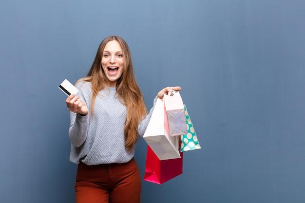 Joven mujer bonita con bolsas de compras contra azul con un copyspace