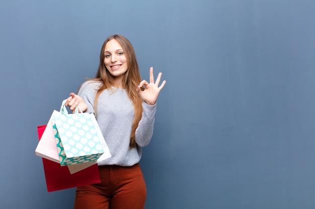 Joven mujer bonita con bolsas de compras contra la pared azul