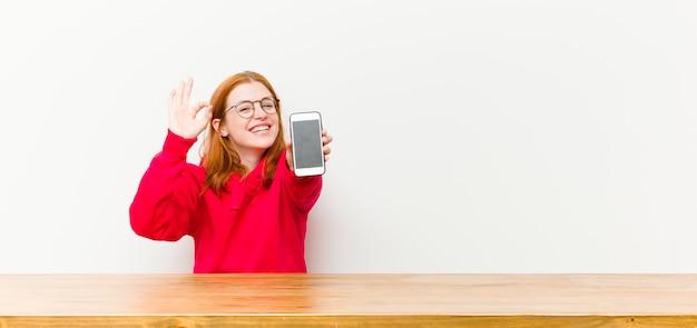 Joven mujer bonita cabeza roja delante de una mesa de madera con un teléfono móvil