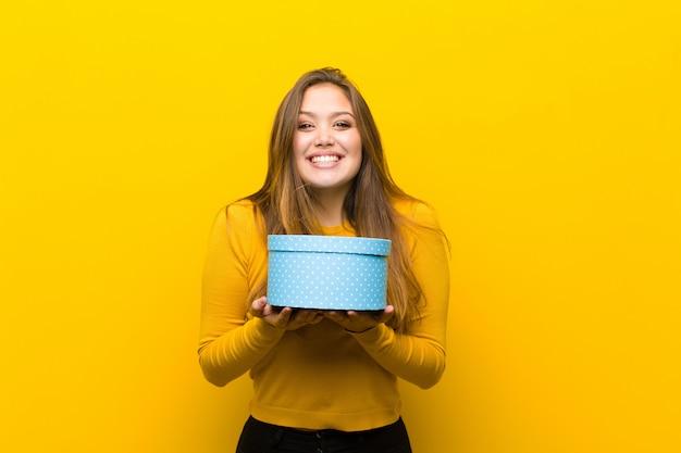 Joven mujer bonita con una caja de regalo contra la pared naranja