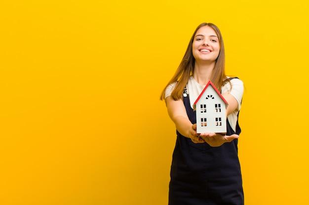 Joven mujer bonita con una casa modelo