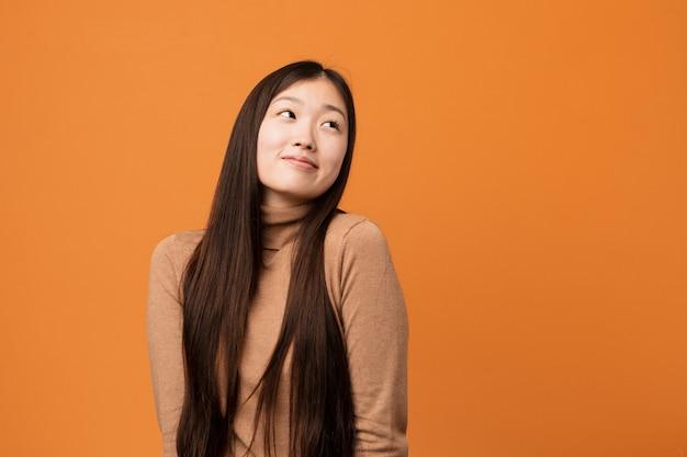 Joven mujer bonita china soñando con lograr objetivos y propósitos