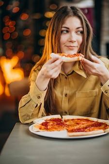 Joven mujer bonita comiendo pizza en un bar