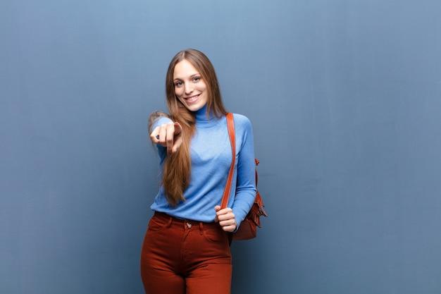 Joven mujer bonita contra la pared azul con un espacio de copia