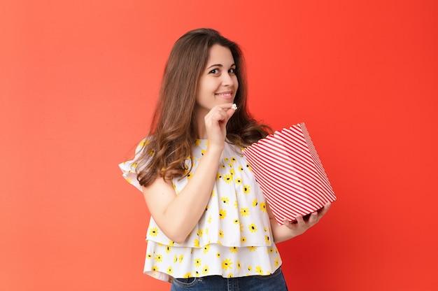 Joven mujer bonita contra la pared roja con un cubo de palomitas de maíz