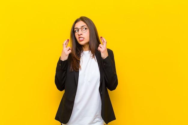 Joven mujer bonita cruzando los dedos con ansiedad y esperando buena suerte con una mirada preocupada contra la pared naranja