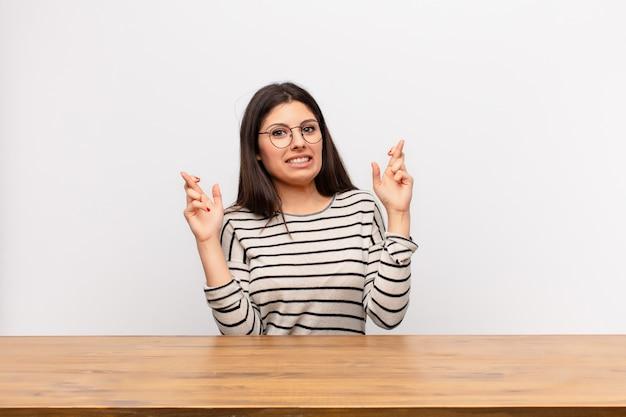 Joven mujer bonita cruzando los dedos con ansiedad y esperando buena suerte con una mirada preocupada sentado en una mesa