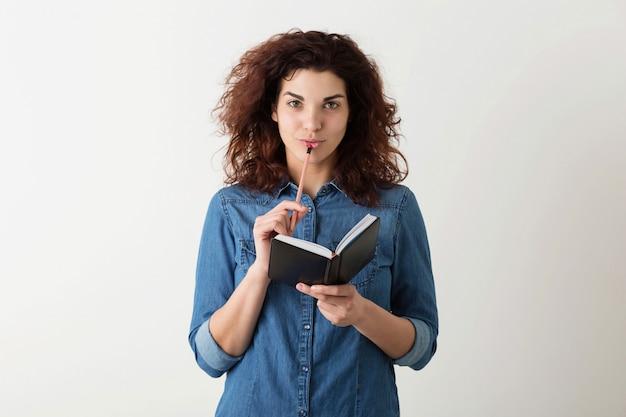 Joven mujer bonita con cuaderno, lápiz en los labios, pensando, sonriendo, cabello rizado, pensativo, feliz, aislado