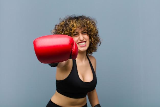 Joven mujer bonita deportiva vistiendo ropa de fitness y guantes de boxeo