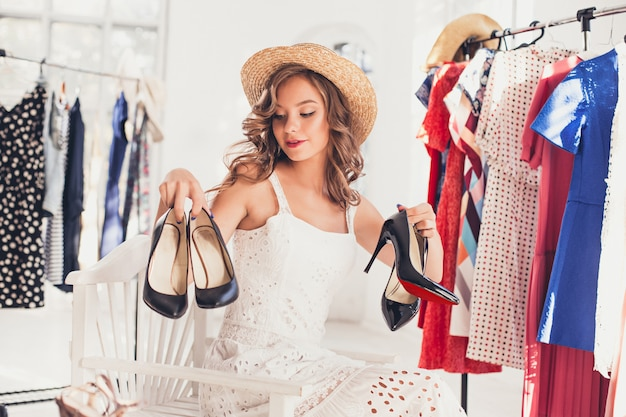 La joven mujer bonita eligiendo y probándose zapatos modelo en la tienda