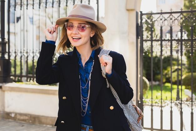 Joven mujer bonita con estilo sonriendo, asombrada, sorprendida, feliz, vestida con abrigo azul oscuro y jeans