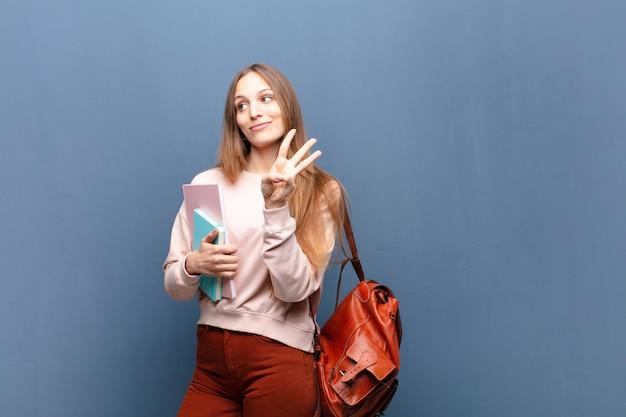 Joven mujer bonita estudiante con libros y bolsa contra azul con un copyspace