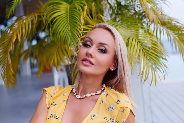 Joven mujer bonita feliz tranquila caucásica con maquillaje de noche brillante con vestido amarillo de verano y collar de conchas de mar