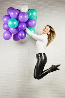 Joven mujer bonita con globos de colores