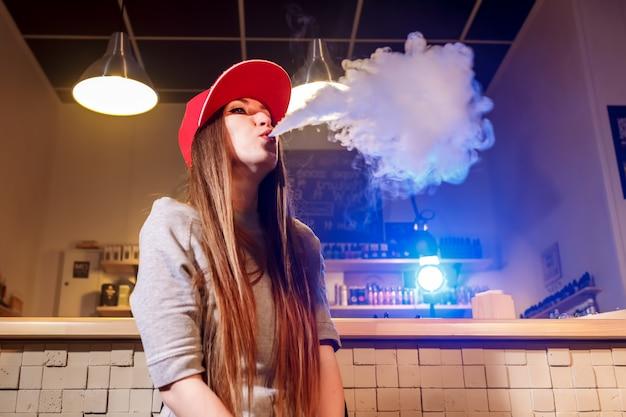 Joven mujer bonita con gorra roja fumar un cigarrillo electrónico en la tienda de vape